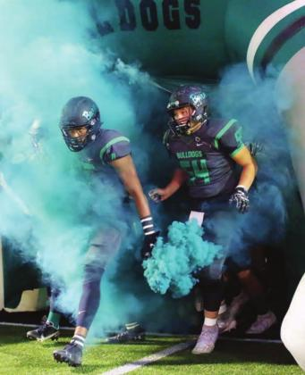 Devonte Miller and Colton Davidson emerge from the tunnel through green smoke at the Dawgs district home opener in Burnet on Friday. Wayne Craig/Clear Memories