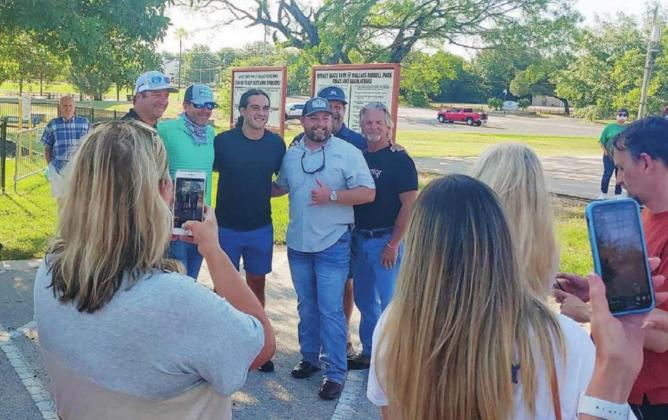 Greg Kelley (third from left), Jake Brydon (third from right) and other members of the Gregory Raymond Kelley (GRK) Foundation pose for photos at a Burnet park during a rally to protest the hiring of former Cedar Park Police Chief Sean Mannix. The GRK Foundation was established after Kelley was wrongly convicted six years ago. Contribtued/Teresa Hernandez