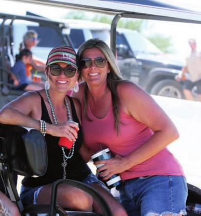 At the right and above, Shelly Laird and Ashley Reutebuch take a break from shooting clays to enjoy beverages and the shade of a golf cart at the Shoot for Coop tournament Saturday, June 13.